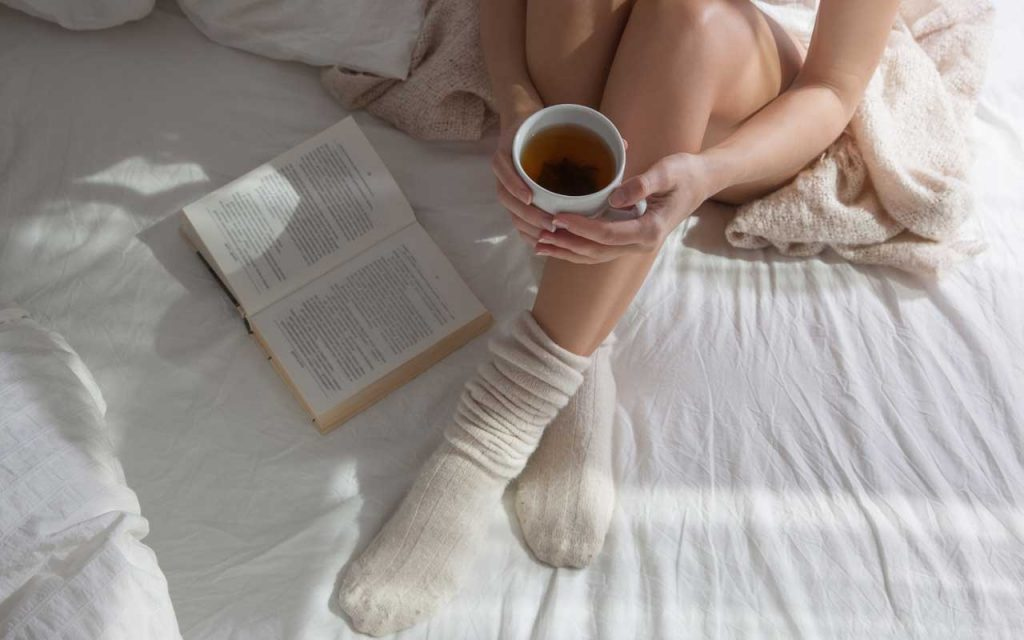 reading a book and drinking tea - self care essentials